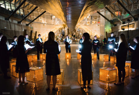 ORA Singers in a circle performing in low light with candlelit boxes in front of them