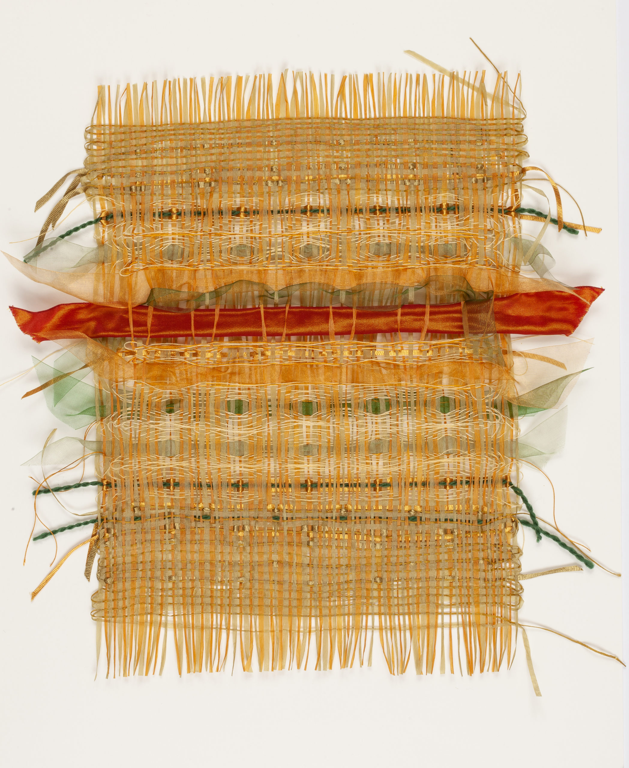 A hand woven weavescape in golds, red and green