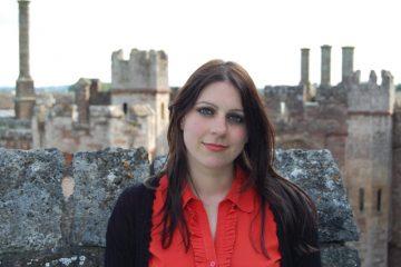 Historian Dr Janina Ramirez standing in front of Berkeley Castle